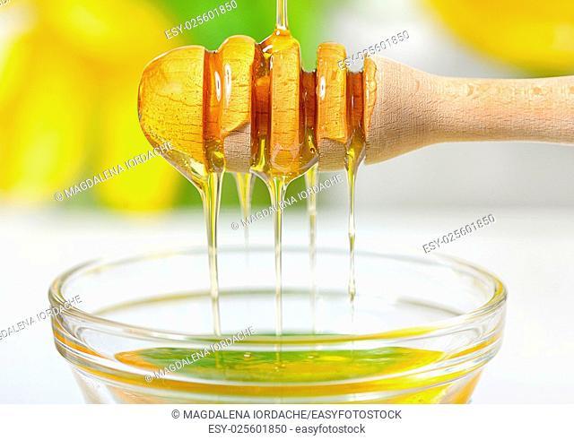 Golden honey dripping from dipper