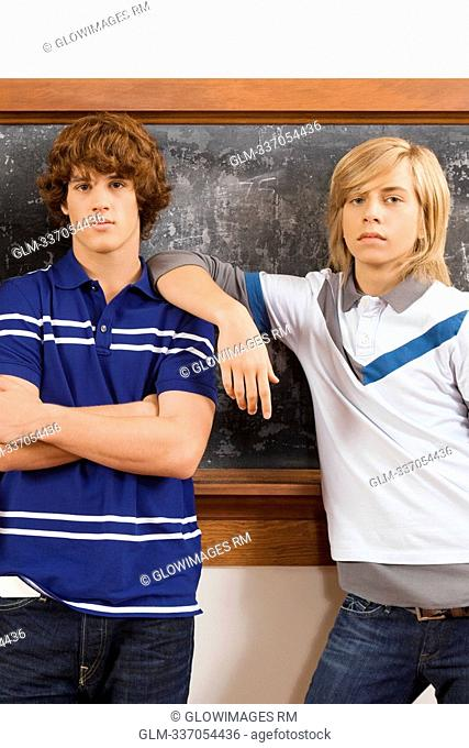 Two teenage boys standing in front of a blackboard