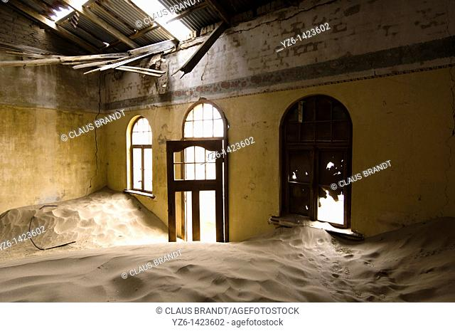 Room of an abandoned house filled with sand, Kolmanskop ghost town near Luederitz, Namibia