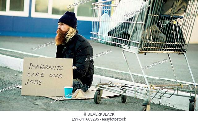 Bearded young homeless man with cardboard sitting near shopping cart and drinks alcohol at cold day. Immigrants crisis in Europe