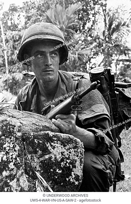 Vietnam: March, 1968 A 101st Airborne soldier crouches behind a rock as he searches for a sniper in the trees ahead