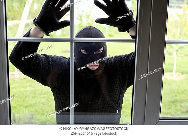 Russia. The culprit in the mask at the window of the apartment