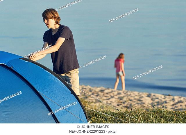 Young man putting tent up