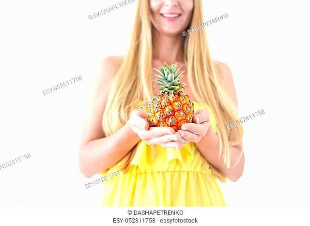 Portrait of a pretty young woman in yellow dress and straw hat holding fresh pineapple
