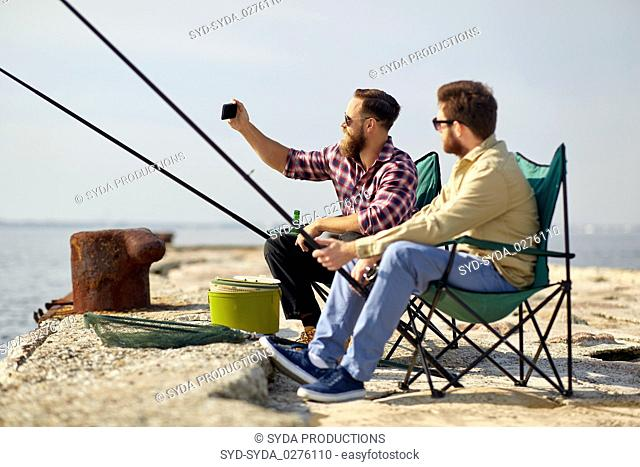 friends fishing and taking selfie by smartphone