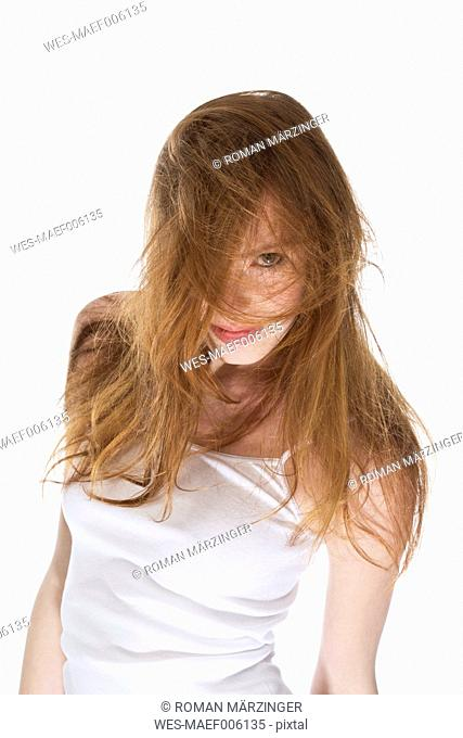Young woman with wind swept hair againt white background, close up