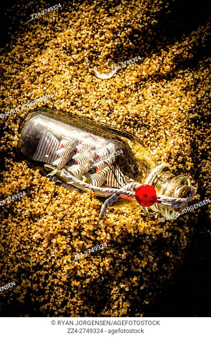 Close-up of ship in glass bottle on brown sand. Quicksand bottled boats