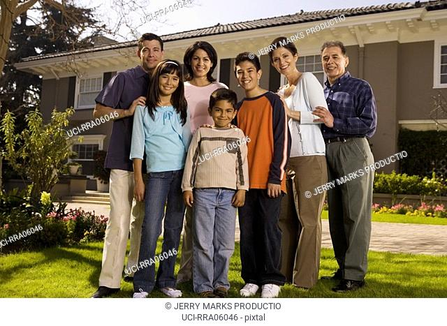 Family standing in front yard of suburban home