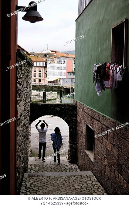 Young couple walking through one of the alleys that accesses the port of Llanes, Asturias. Spain