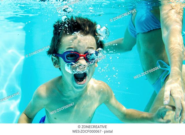Young boy under water, air bubbles