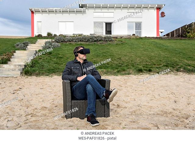 Man sitting in armchair on the beach wearing VR glasses