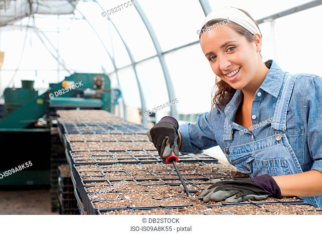 Young woman planting seeds in garden centre, portrait