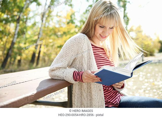 Young woman reading book while sitting at park