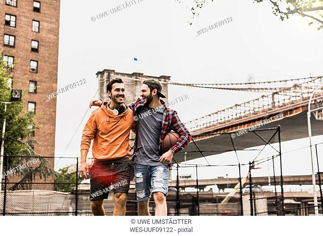 USA, New York, two happy young men on an outdoor basketball court