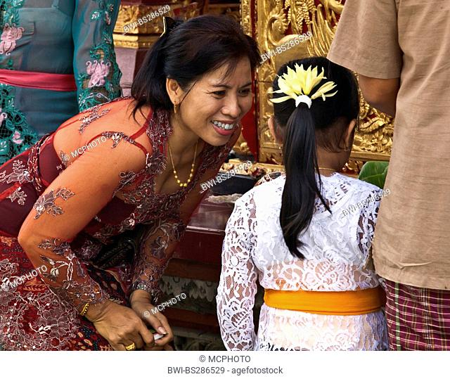 BALINESE WOMAN and daughter at PURA TAMAN SARASWATI during the GALUNGAN FESTIVAL, Indonesia, Bali, Ubud