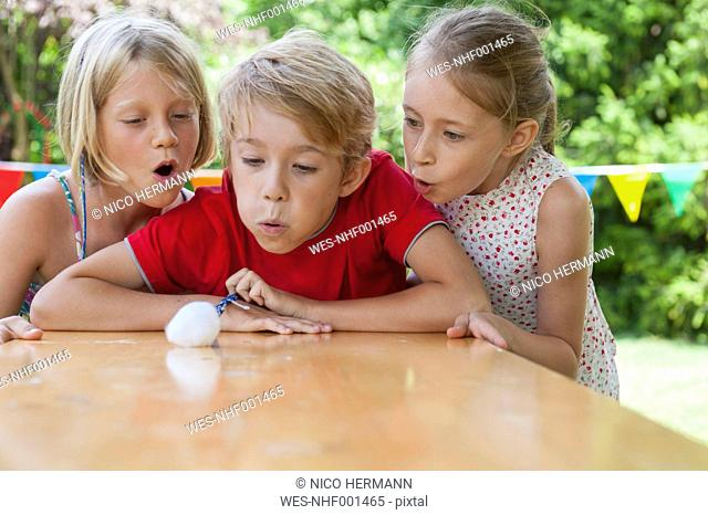 Children blowing cotton ball on garden table