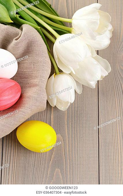 easter eggs and white tulips on wood table, rustic style