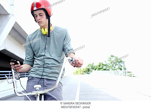 Teenage boy on bicycle with cell phone