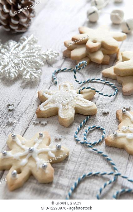 Iced homemade snowflake shaped christmas biscuits being treaded with blue and white bakers twine on a white wash wooden surface surrounded by Christmas tree...