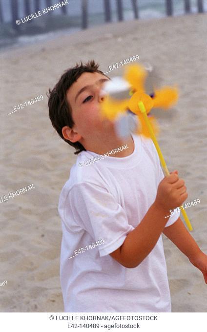 Boy blowing a windmill toy