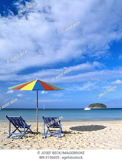 A sunshade and beach chairs on Kata Beach, the island of Ko Pu at the back, Andaman Sea