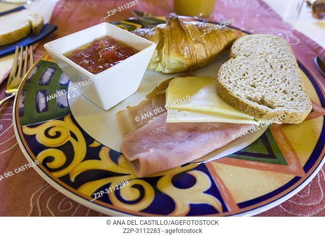 Breakfast plate cheese ham bread croissant and fresh tomato puree