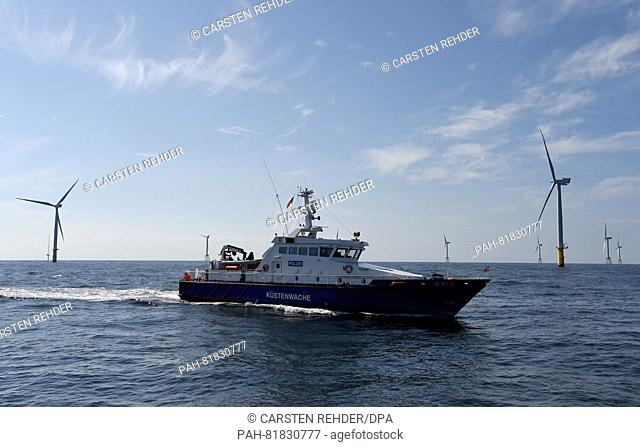 The police vessel 'Sylt' seen next to wind turbines located on the North Sea some 30 kilometres off Helgoland, Germany, 04 July 2016