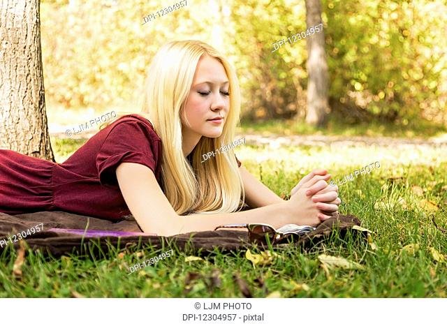 A young woman with long blond hair spending personal time in Bible study and praying outdoors in a park in autumn; Edmonton, Alberta, Canada