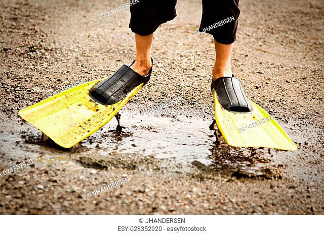 Cropped view on feet of kid walking through muddy puddle of water in black and yellow diving flippers