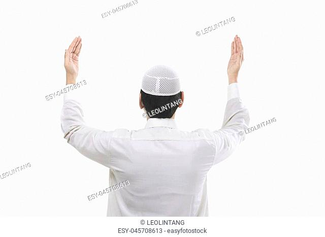 Back view of young muslim man praying isolated over white background