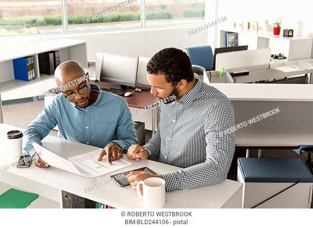 Men reading paperwork in office