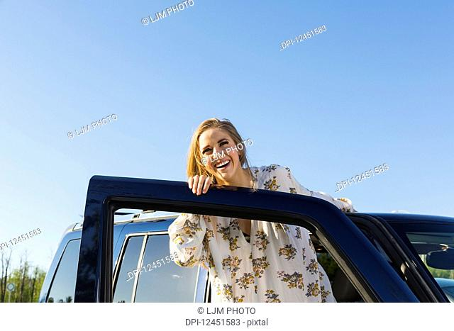 Young woman with long blond hair posing for the camera at the open door of a vehicle; Edmonton, Alberta, Canada