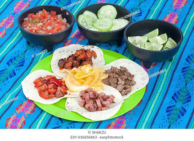 Taco plate display of four corn tortillas with different kinds of barbecued meat and onion with condiment bowls of fresh Mexican salsa, cucumbers