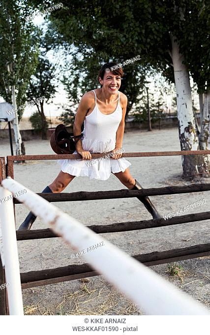 Portrait of happy woman with riding helmet leaning on gate of riding ring