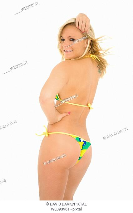 Beautiful and sexy caucasian woman in her early 20s posing in a Brazilian bikini on a white background