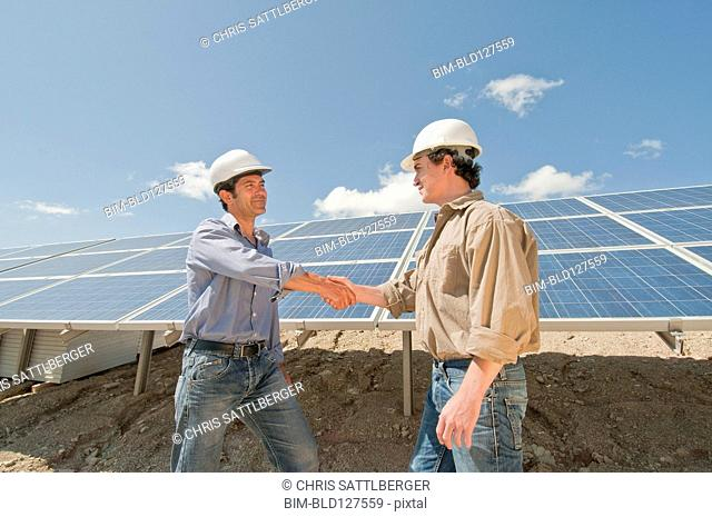 engineers shaking hands in solar plant