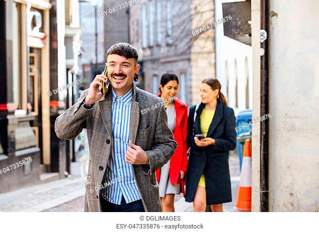 Businessman is walking through the city to go to work. He is well dressed and is talking on the phone, while two women can be seen in the background walking...