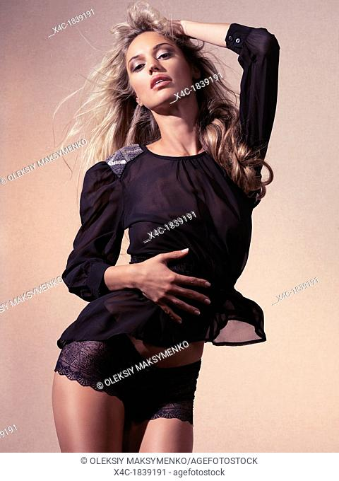 Young beautiful woman with long blond hair wearing black lace underwear and see-through top isolated on beige background