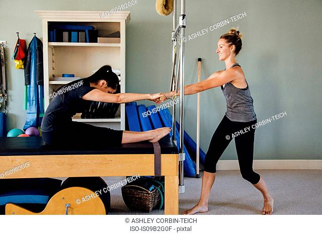 Woman and personal trainer using pilates reformer