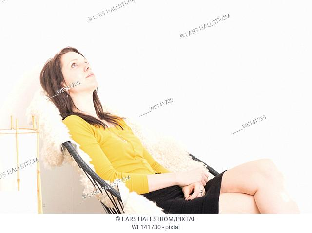 Woman sitting in chair, relaxing and staring at the ceiling. Concept of boredom, loneliness and contemplation