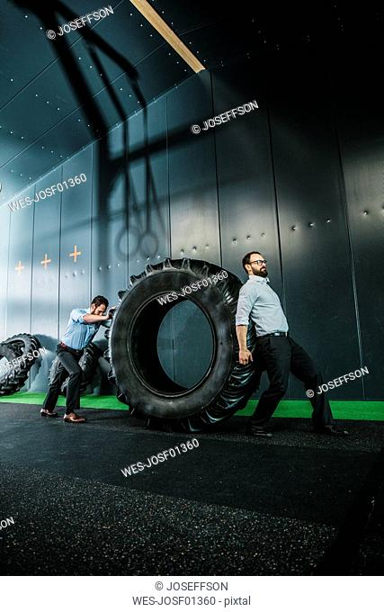 Two businessmen pushing and pulling truck tire