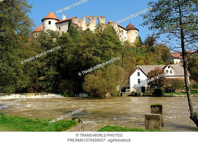 Slovenia, Prov. Suha Krajina, Zuzemberk, River Krka and castle ruin on the hill