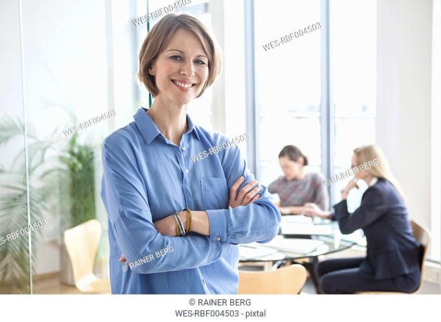 Portrait of smiling businesswoman with colleagues in background