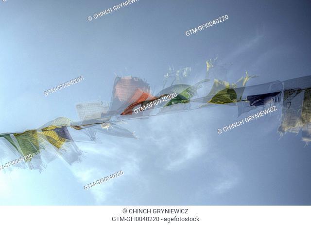 Tibetan Prayer Flags Fluttering Against Blue Sky