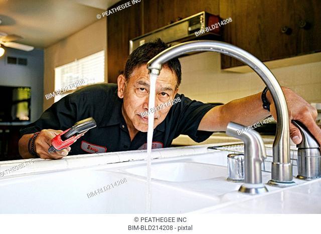 Pacific Islander plumber examining sink in kitchen
