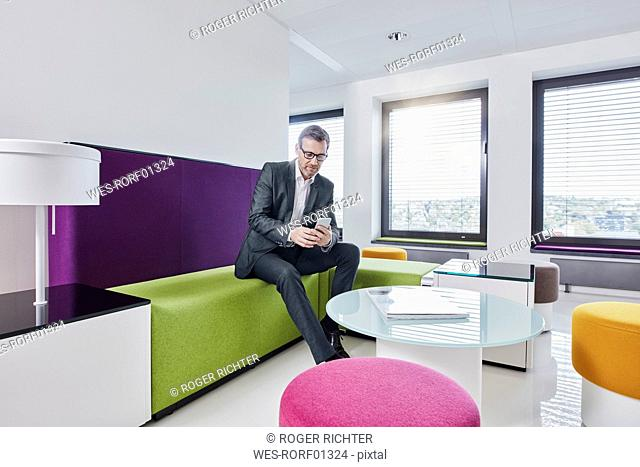 Businessman using smartphone in office lounge