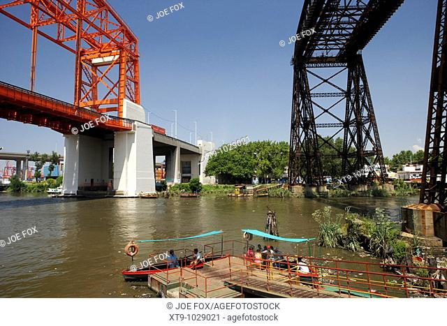 small boats acting as a ferry for local people across the riachuelo river beneath soon to be refurbished old puente transbordador bridge la boca capital federal...