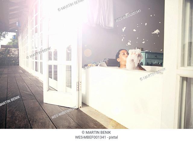 Woman in bathtub blowing foam
