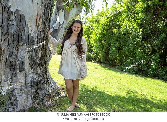 Teenage girl standing by a tree in San Diego, California