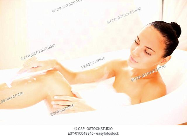 Making her legs soft and silky. Side view of beautiful young woman shaving her legs while lying in bathtub
